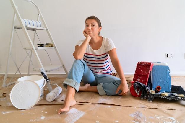 Женщина с инструментами для ремонта, сидя на полу.