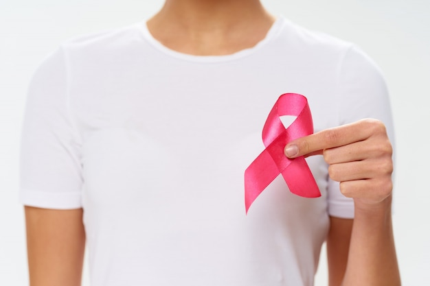 Woman with ribbon in her hands, breast cancer day, female organ cancer, cancer day