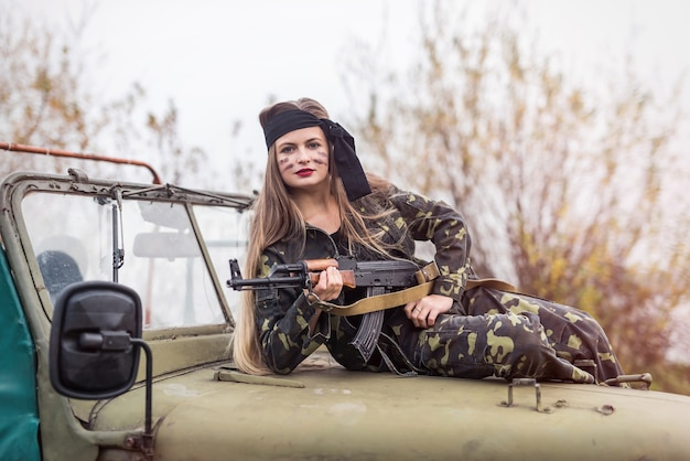 Woman with rifle posing on military car