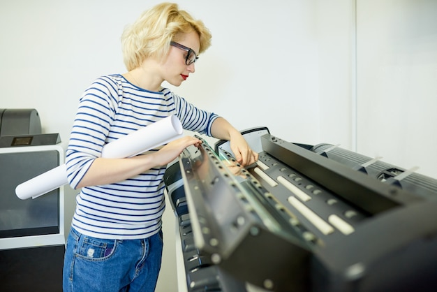 Woman with roll of paper checking printer
