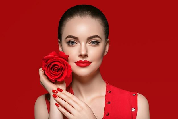 バラの花を持つ女性。赤い背景の上に美しいバラの花とサロンの髪型を持つ美しさの女性の肖像画。スタジオショット。