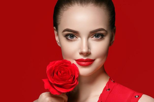 장미 꽃을 가진 여자입니다. 빨간 배경 위에 아름다운 장미 꽃과 살롱 헤어스타일을 한 미인 여성 초상화. 스튜디오 촬영.