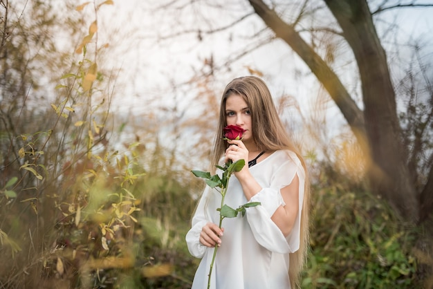 湖の水に対してポーズをとってバラの女性