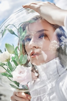 Woman with a round aquarium on her head holds flowers near her face. concept of a girl cosmonaut and nature. protection of nature and ecology
