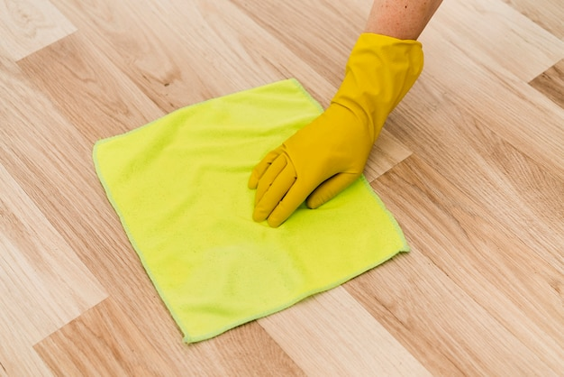 Woman with rubber glove cleaning the floor