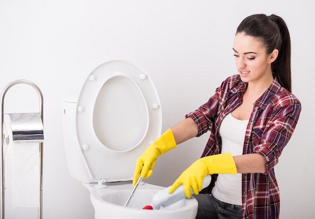 Woman with rubber glove is cleaning toilet bowl using brush.