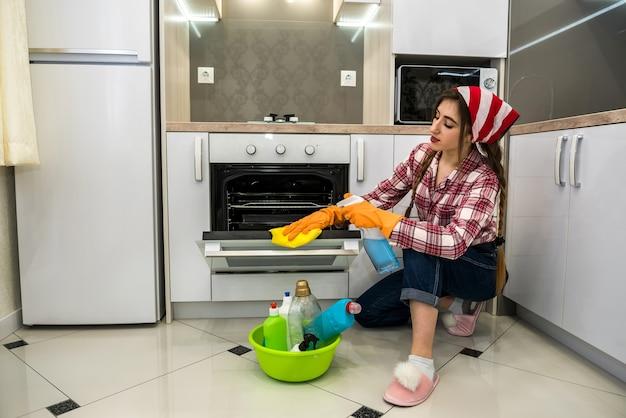 ゴム手袋と消毒剤を持った女性が台所の床を洗います。
