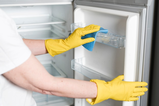 Woman with rubber gloves cleaning fridge