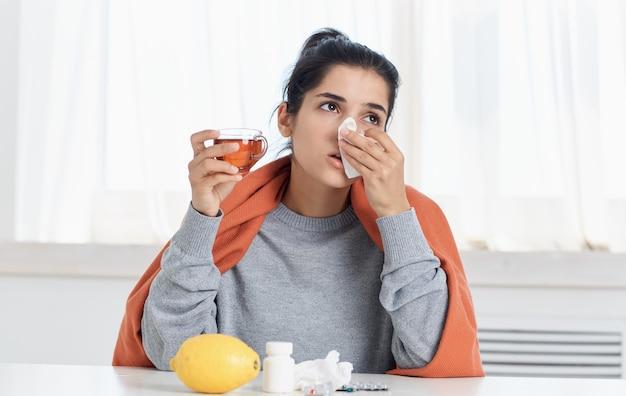 Женщина с проблемами здоровья насморк горячий напиток в чашке с салфеткой в руке.