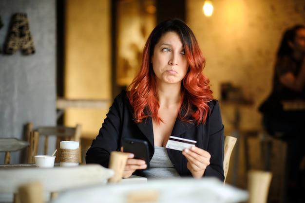 Женщина с грустным лицом смотрит на свой мобильный телефон, держа в руке кредитную карту