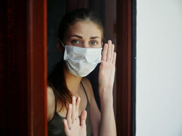 医療マスクで悲しい表情を持つ女性は、ロックダウンウィンドウで手を握ります