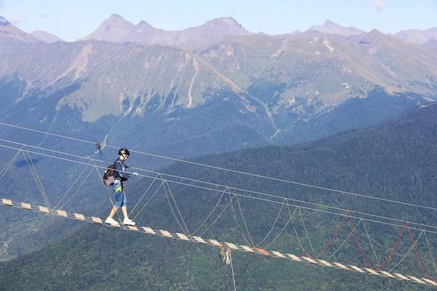 安全装置を持った女性が山の表面に向かって吊り下げ道路を進む