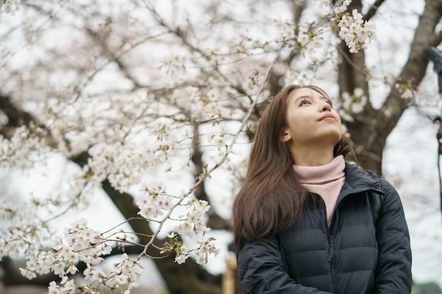 Женщина с цветком сакуры или японской вишни на ветвях деревьев. весенние цветы.