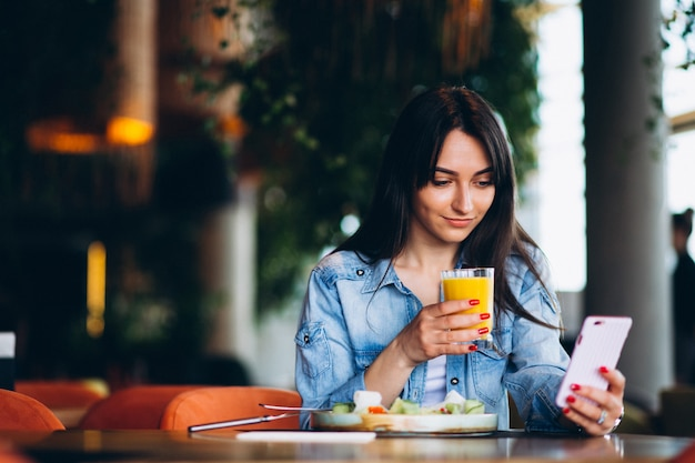 Woman with salad and phone