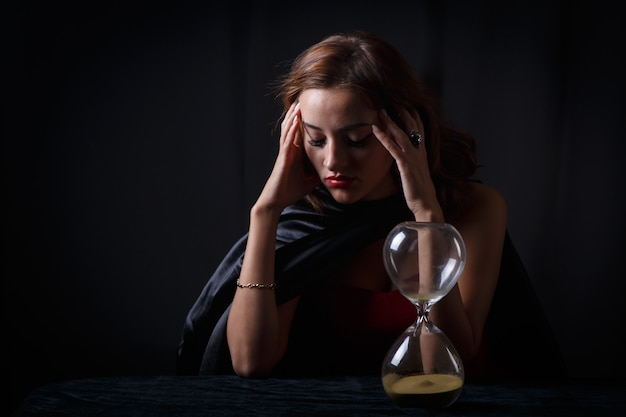 Женщина с песочными часами на столе