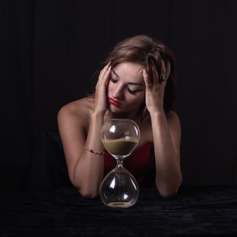テーブルの上の砂の時計を持つ女性
