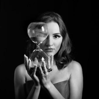 黒と白で撮影された砂の時計を持つ女性