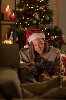 Woman with santa hat holding dog next to laptop