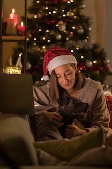 Женщина в шляпе санта держит собаку рядом с ноутбуком