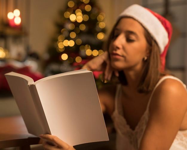 本を読んでクリスマスにサンタの帽子をかぶった女性
