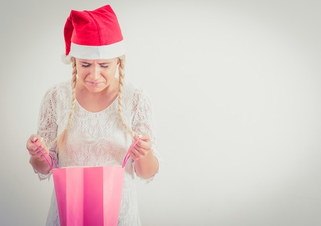 Woman with santa hat opening the christmas gift