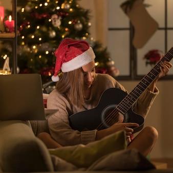 ノートパソコンの前でギターを弾くサンタ帽子を持つ女性