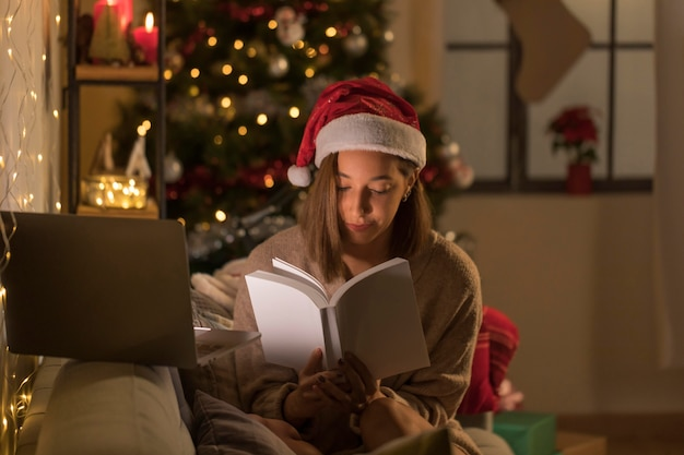 Woman with santa hat reading book in front of laptop