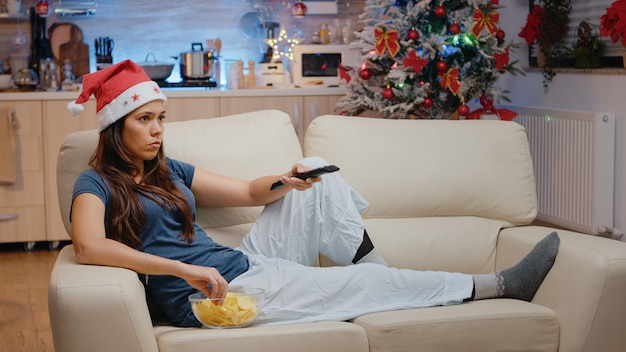Donna con cappello da babbo natale che cambia canale usando il telecomando della tv