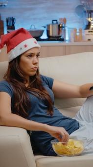 テレビのリモコンを使用してチャンネルを切り替えるサンタ帽子を持つ女性