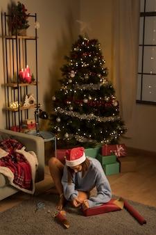 Женщина в шляпе санта-клауса упаковывает подарки на рождество