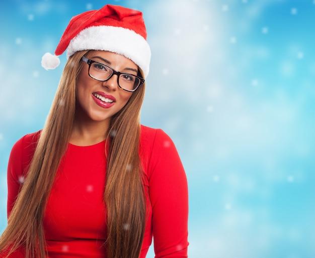 サンタの帽子と雪の背景を持つ女性