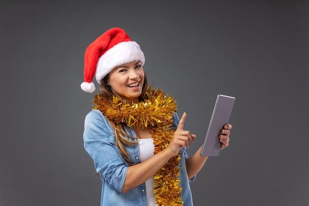 クリスマスイブにタブレットを使用して頭にサンタの帽子をかぶった女性。
