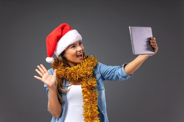 Женщина в шляпе санта-клауса на голове, с рождественскими украшениями на шее с видеозвонком.