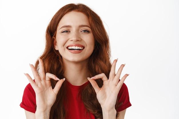 Женщина с удовлетворенными эмоциями, показывающая знак «окей, ок», хвалить хорошую работу, одобрять и что-то нравиться, говорить «да». согласен и рекомендую по белому.