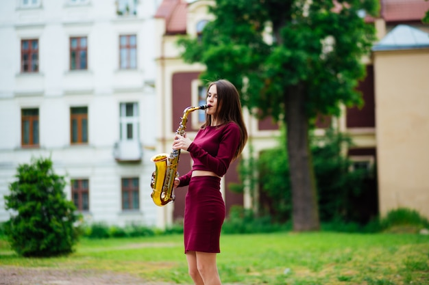Woman with saxophone on street