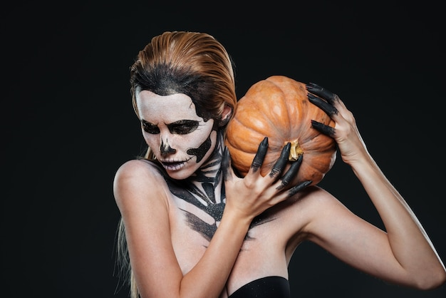 Woman with scared halloween makeup holding pumpkin over black background Premium Photo