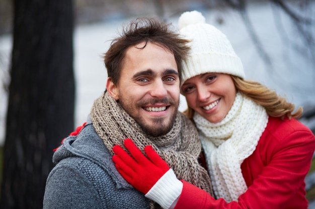 Woman with scarf and wool hat hugging her boyfriend