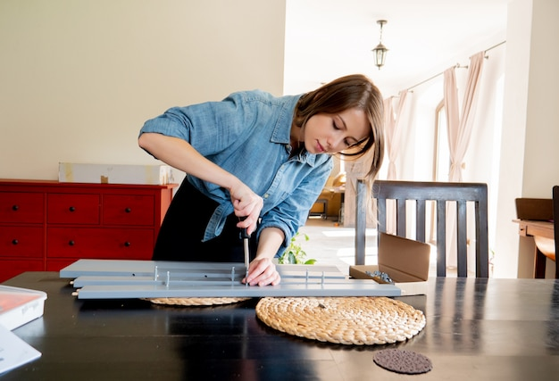 Woman with screwdriver instaling a furniture at home personally