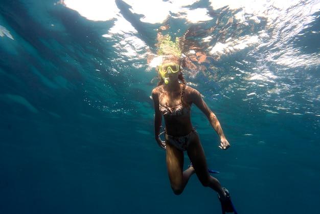 海で泳ぐスキューバギアを持つ女性