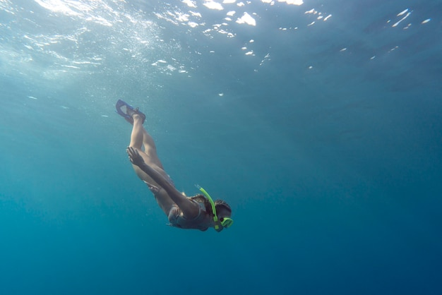 Woman with scuba gear swimming in the ocean