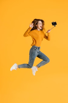 Woman with selfie stick jumping