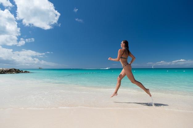 화창한 날 자연 환경에서 하얀 모래, 청록색 물, 푸른 하늘이 있는 바다 해변에서 수영복을 입은 섹시한 몸매를 가진 여성. 선탠, 목욕. 여름 방학. 여유롭고 활동적인 레저