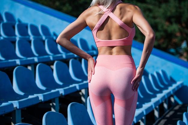 Женщина с сексуальными ягодицами фитнеса в спортивной тренировке на стадионе, здоровом образе жизни и диете.