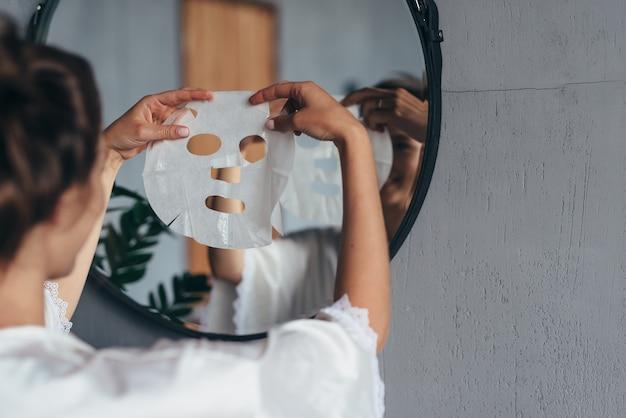 그녀의 얼굴에 적용하기 전에 화장실에서 그녀의 손에 시트 마스크를 가진 여자.