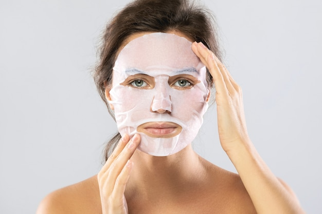 Woman with a sheet moisturizing mask on her face isolated on gray