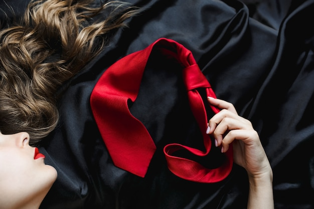Woman with shiny hair holds a red tie lying on black bed