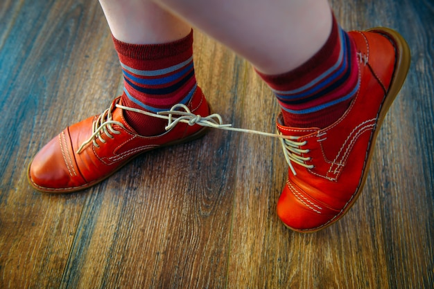 Woman with shoelaces tied together. red funny shoes on wooden background.