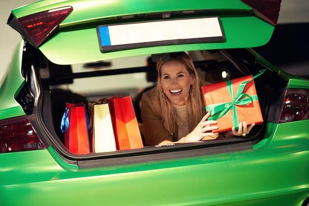 Женщина с хозяйственными сумками и рождественскими подарками лежит в багажнике на стоянке