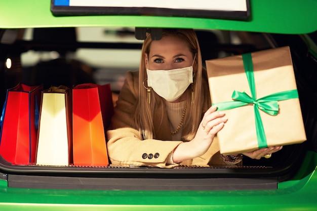 Женщина с сумками и рождественскими подарками в маске лежит в багажнике на стоянке