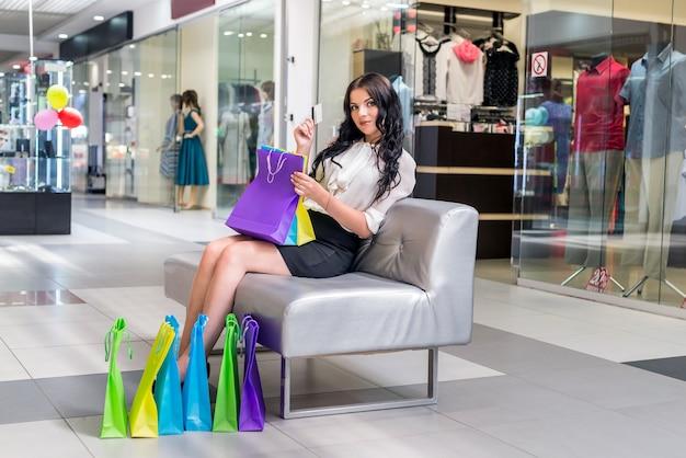 쇼핑백과 신용 카드 소파에 앉아 여자